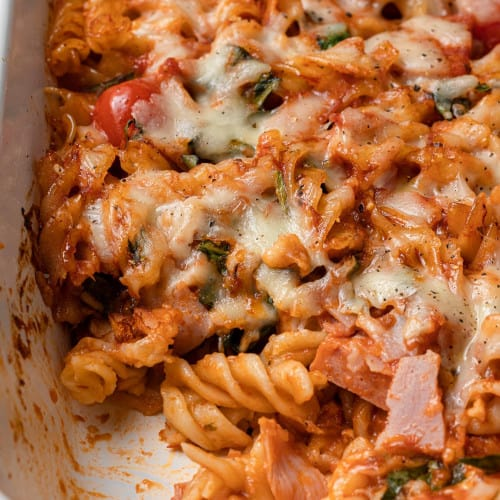 Pasta in a baking dish with pizza sauce, ham, cheese, tomatoes, and spinach. A scoop has been removed.