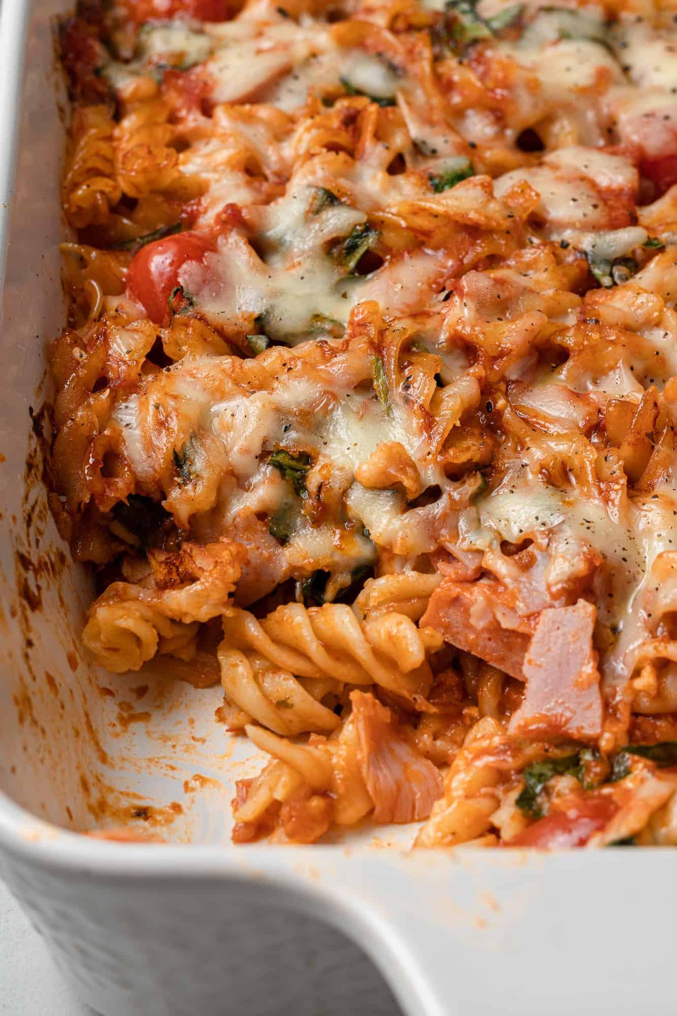 Pasta bake with a scoop taken out to show ingredients.