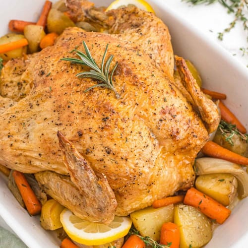 Roasted chicken in a white baking dish with potatoes and carrots.