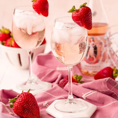 Two stemmed glasses with rose spritzers, garnished with strawberries.