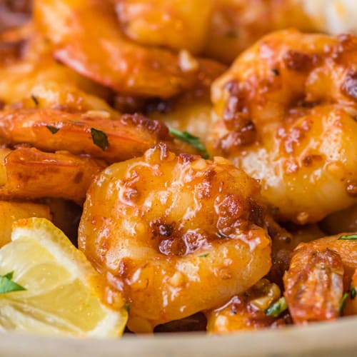 Close up of cooked shrimp with spicy honey sauce and bits of crunchy garlic.