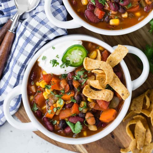 Overhead view of chili in a white bowl with fritos, sour cream, jalapeno.