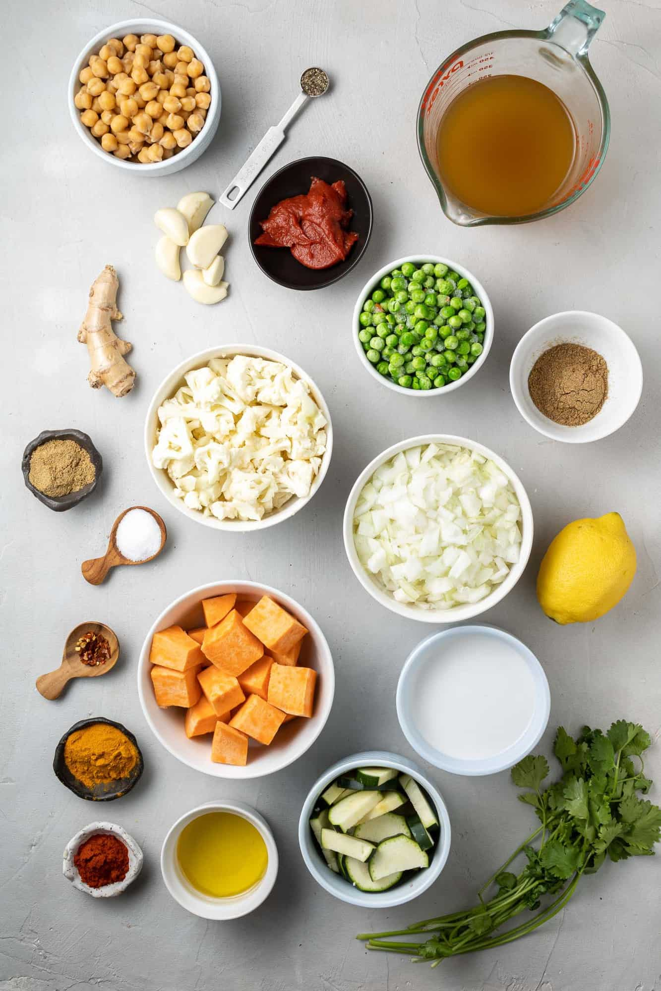 Overhead view of ingredients needed including spices, chickpeas, cauliflower, sweet potatoes, and peas.