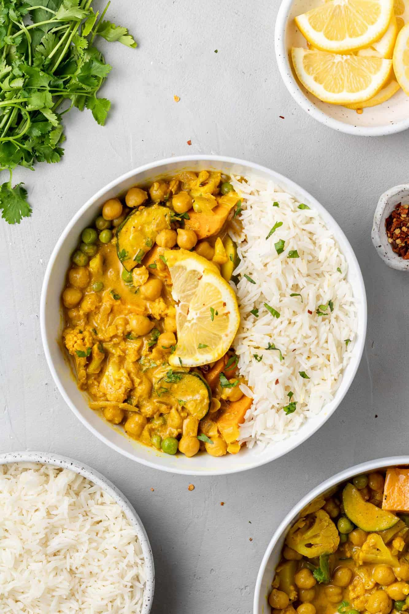 Overhead view of curry in a bowl with rice, sprinkled with cilantro.