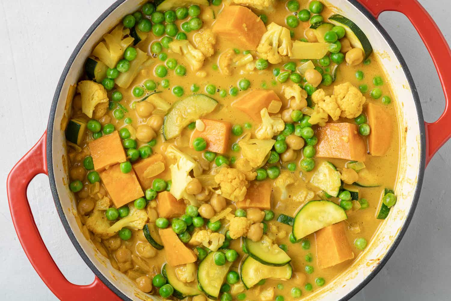 Peas added to a yellow orange curry in a red dutch oven.