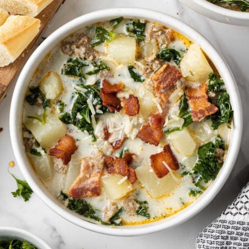 Overhead view of zuppa toscana soup in a white bowl garnished with crispy bacon.