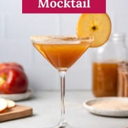 """Brown drink in martini glass, text overlay reads """"ginger apple cider mocktail."""""""