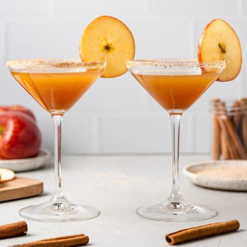 Two apple cider mocktails garnished with round apple slices.
