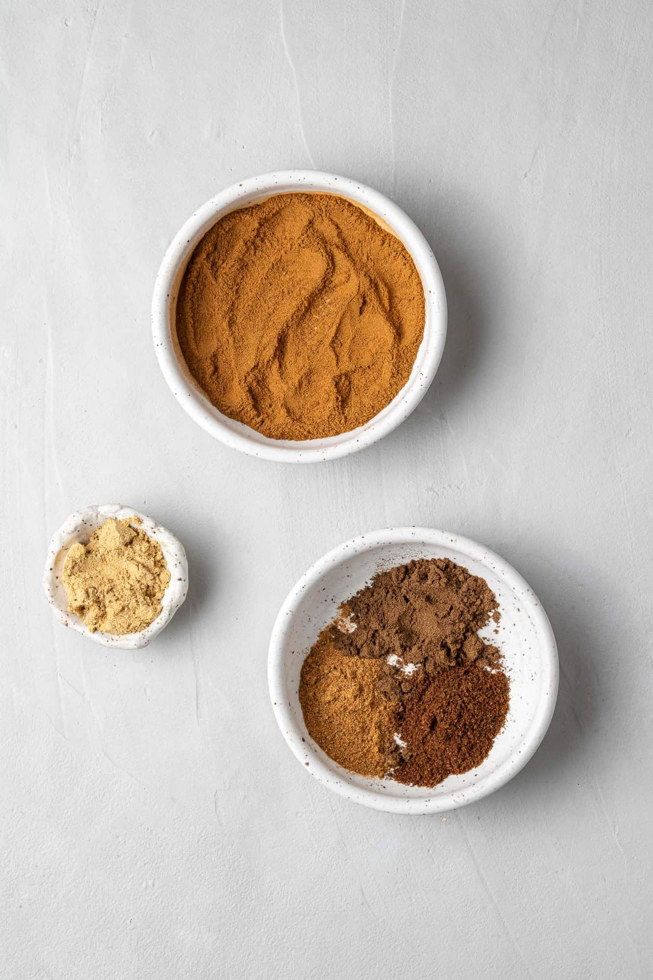 Spices in separate bowls on a light grey background.