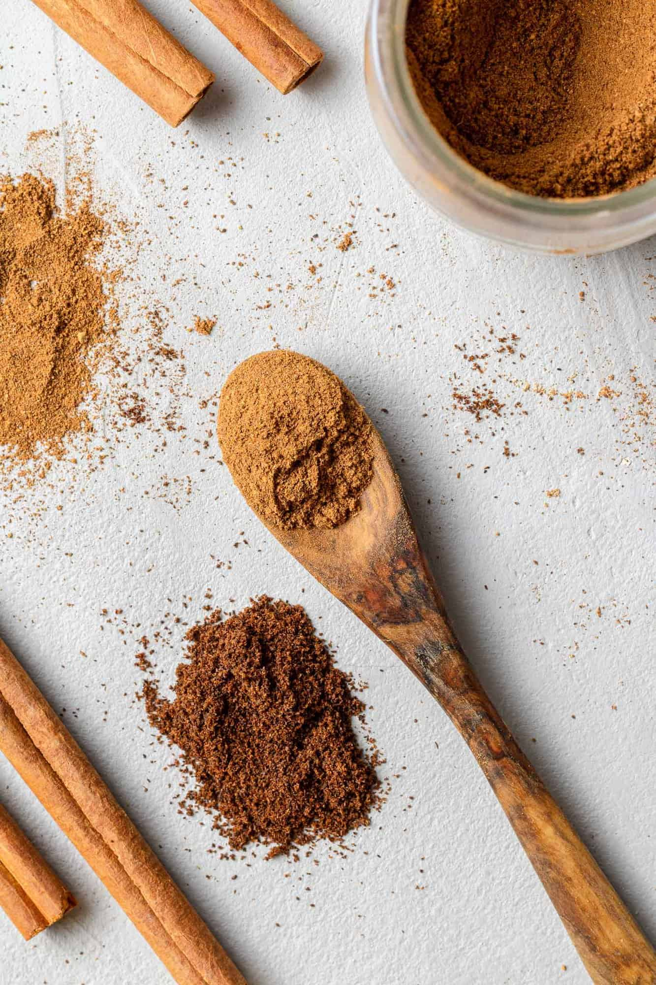 Brown spices on a tiny wooden spoon, other spices nearby.