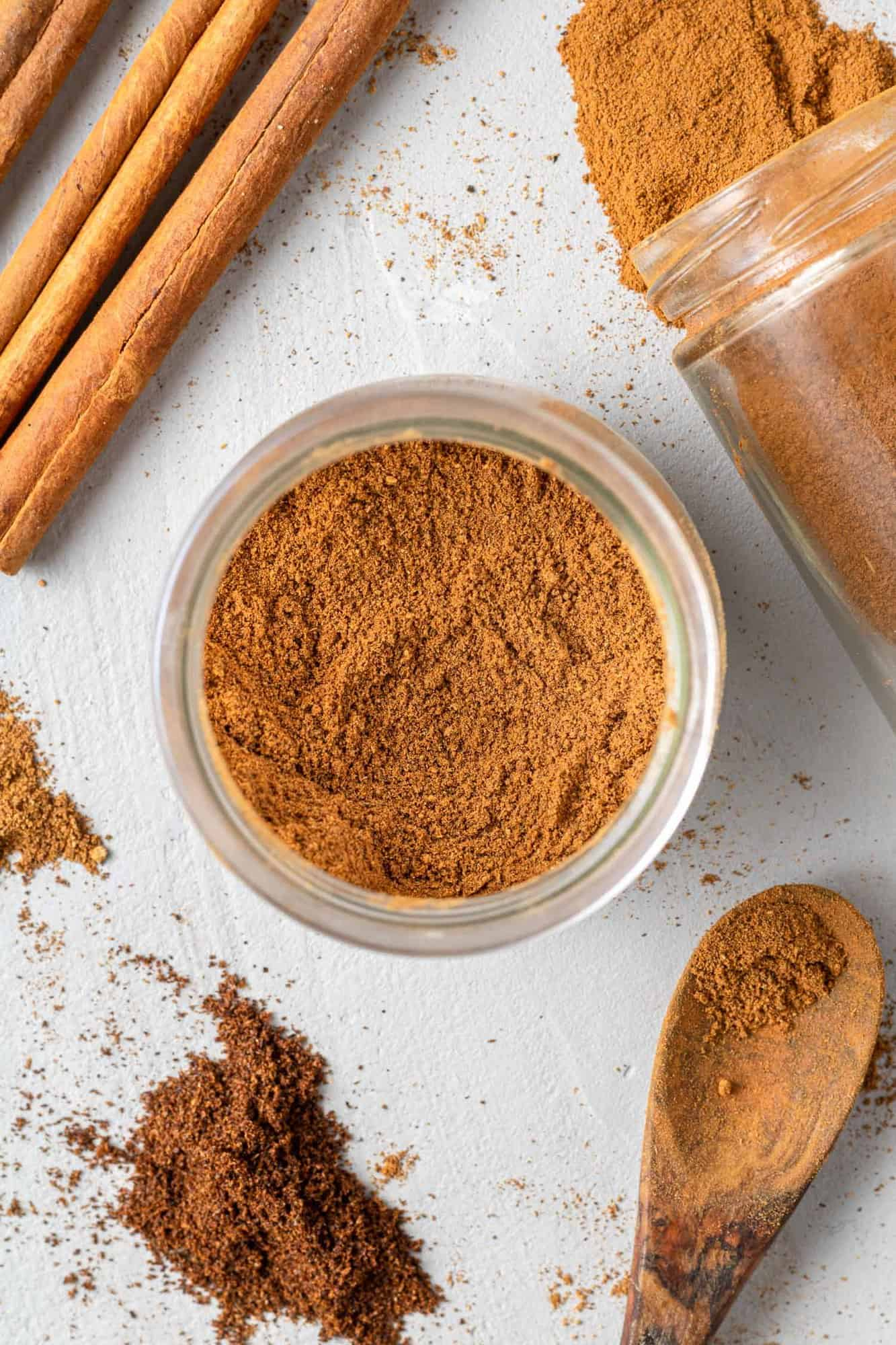 Homemade pumpkin spice in a jar, with ingredients surrounding it.