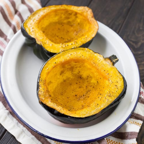 Two acorn squash halves on a white platter, both have been roasted and seasoned with salt and pepper.