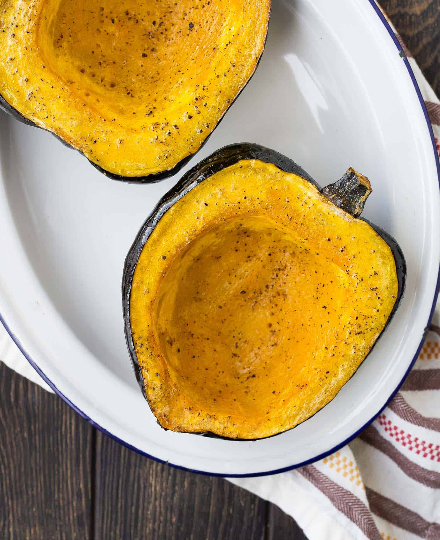 Overhead view of acorn squash half, roasted with pepper.