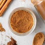 Overhead view of pumpkin pie spice in a small jar, cinnamon sticks nearby.