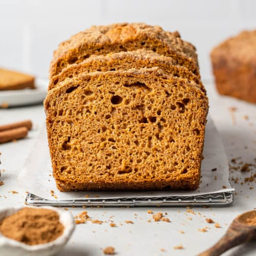 Sliced pumpkin streusel bread with spices around it.