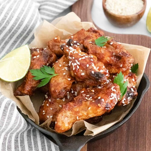 Pan of asian chicken wings sprinkled with sesame seeds and parsley.